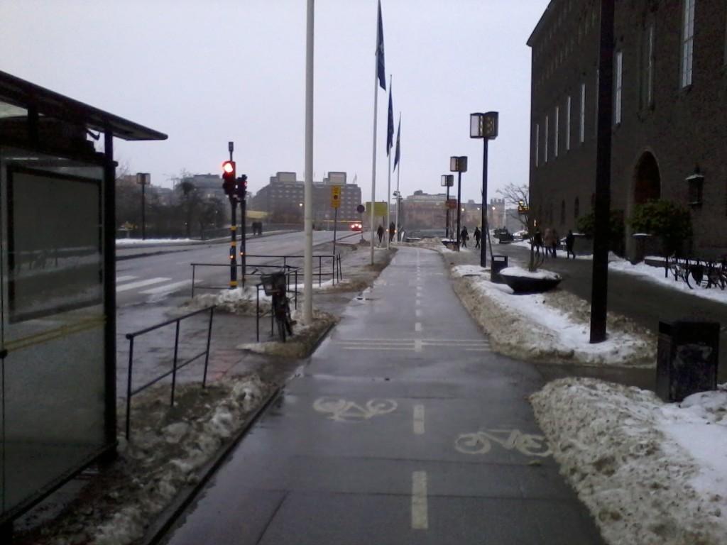 Kuvassa oikealla kaupungintalo. Huomaa kuinka lumitilat saavat olla lumessa. Helsingin Bulevardilla lumitilat on kaavittu puhtaaksi kaarnoja myöden, mutta viereisellä pyörätiellä onkin lupa säilyttää lumikasoja ja muutenkin pyörätie on kaikkea muuta kuin ajettava. (Pyörätien hoidosta vastaa Bulevardilla kaupunki)
