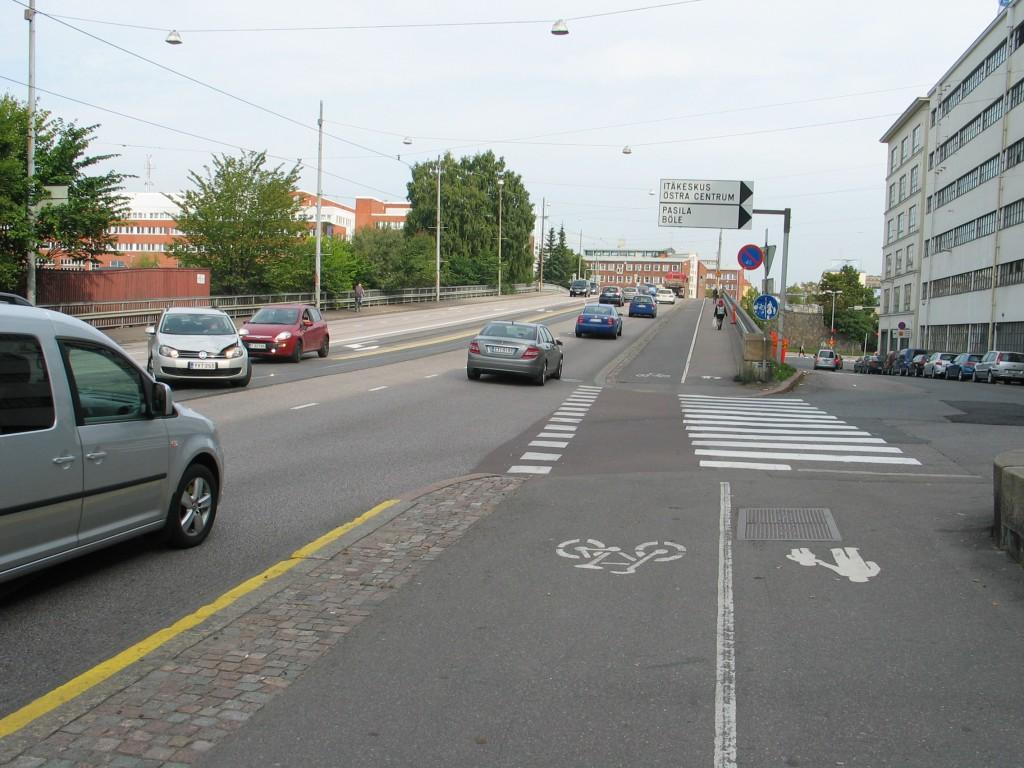 Helsingin vaarallisin pyörätien jatke. Autoja tulee kolmesta suunnasta, joista vain kuvan suunnasta tuleva näkee vastasuuntaisen pyöräilijän hyvin. Muut kaksi ovatkin niitä jotka tulevat päälle. Yksisuuntaisena pyörätienä kaikki kolme autoa näkisivät lähestyvän pyöräilijän. Siitä huolimatta pyörätien jatke pitäsi massata punaiseksi.