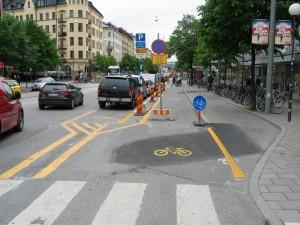 Puolivalmis. Sekava? Oikealla uuden pyörätien tekemisen aikainen reitti (alkuperäisellä pyörätiellä olivat koneet ja tarvikkeet). Keskellä uusi (ottaisivat jo nuo merkit pois). Ja vasemmalla vanha, joka tullaan poistamaan, tai varmaankin muuttamaan pyöräpysäköinniksi. Vanha pyöräpysäköinti jalkakäytäväksi. Kaksi metriä lisää kävelytilaa.