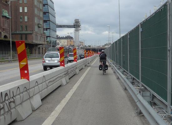 Näinkin voi tehdä. Ajoradalta on erotettu kokonainen kaista pyöräliikenteelle. Jalankululle on oma reitti. Helsingissä esimerkiksi Kulosaaren sillalla pyöräilijät käskettiin tylysti – normikäytännön mukaan – kiertämään Itäväylän toiselta puolelta useiden vuosien ajan. Kuva Tukholmasta.