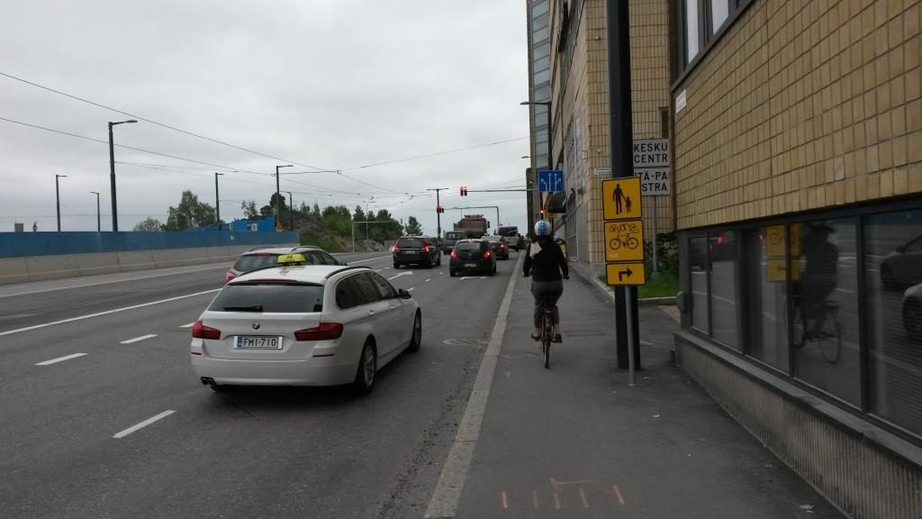 """Alle puolitoista metriä leveä kaksisuuntainen yhdistetty pyörätie ja jalkakäytävä. Pyöräilijöitä yritetään ohjata uudelle kierrolle. """"Nykyistä parempaa ratkaisua emme ole keksineet."""" - Reijo Alaoja (Huomatkaa ajokaistojen leveys!)"""