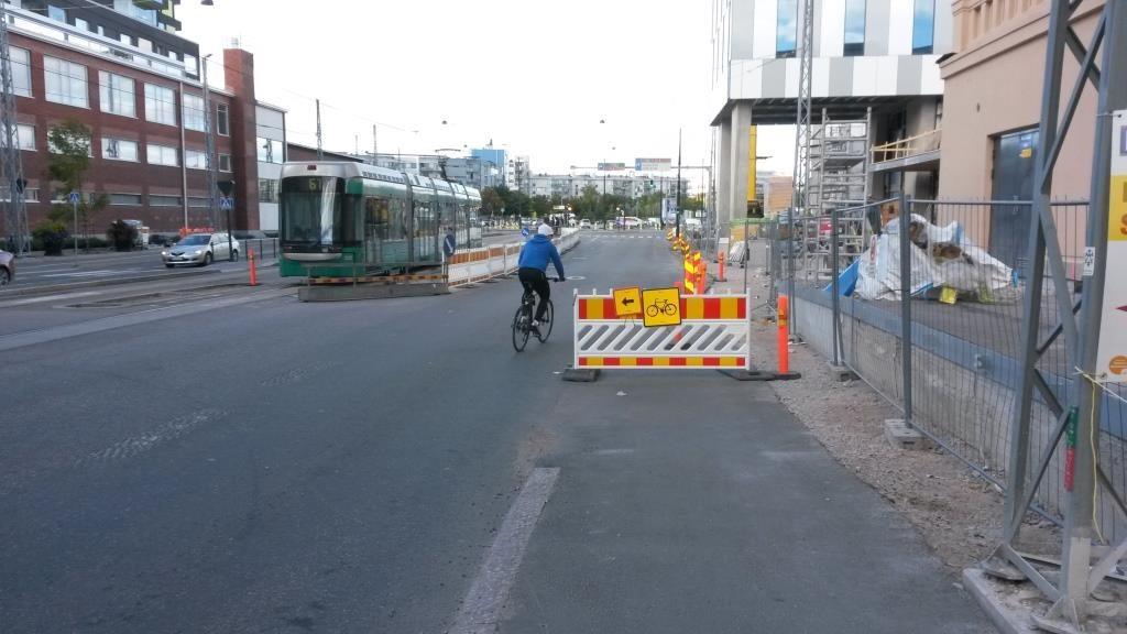 Kävelyn jälkeen aidalla yritetään pakkosiirtää prioriteettien kakkonen: pyöräily pois, jotta pyöräkaista voidaan jyrsiä pois ja siitä tuleva uusi tila antaa yksityisautoille. Kuvassa näkyvä kaivanto on tällä hetkellä ainoa ajoradalla oleva työmaa, minkä takia kaikki pakkokierrot on tehty.